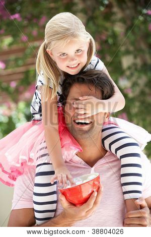 Father Giving Daughter Ride On Shoulders Outdoors Whilst Eating Marshmallows