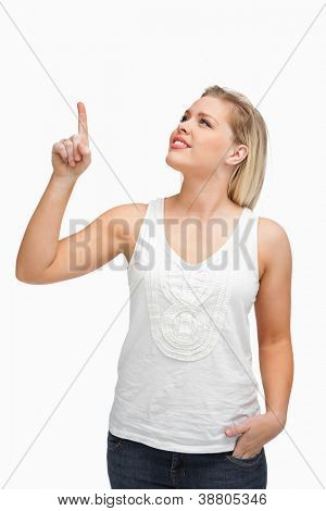Cheerful blonde woman pointing her finger up against a white background