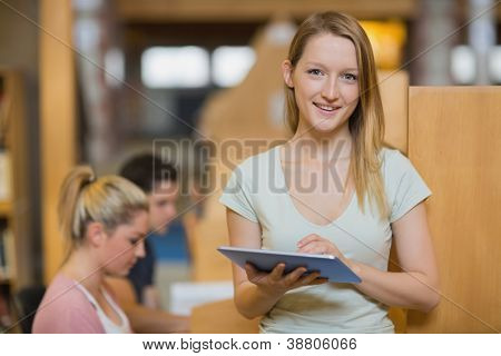 Woman standing holding a tablet computer while smiling at the college library