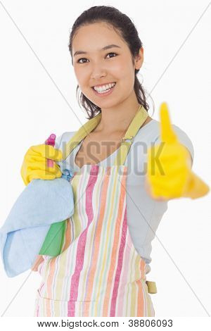 Smiling woman in apron holding cleaning products giving thumbs up