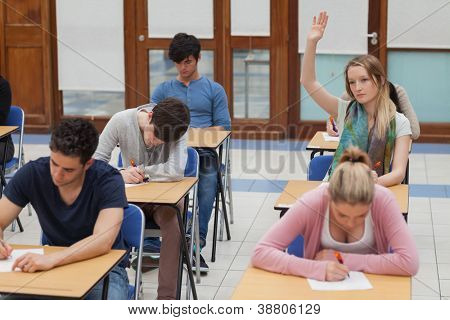 Woman raising hand during exam in exam hall in college