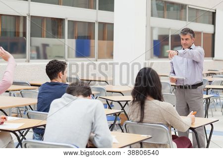 Teacher pointing at student asking question in classroom in college