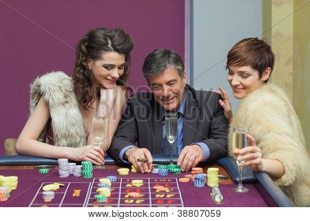 Man and two women talking at roulette table in casino