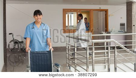 Smiling doctors assistant pushing a wheelchair in a hospital