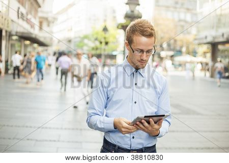 Businessman read news on Tablet Computer, urban street public space