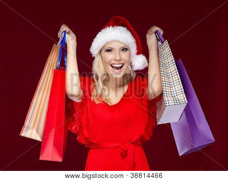 Pretty woman in Christmas cap hands shopping packets, isolated on purple