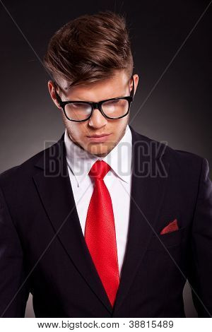 closeup picture of a young business man with eyeglasses looking down, on dark background