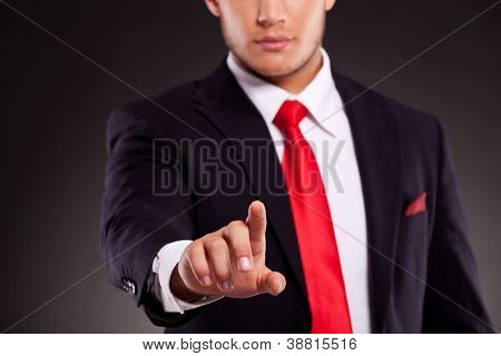 cutout picture of a young business man pushing a button with focus on his finger. against dark background
