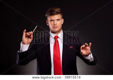 young business man conducting with a stick, while looking at the camera. on dark background