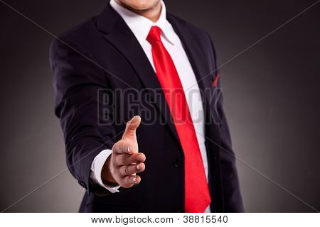 cutout of a business man offering a handshake, on dark background