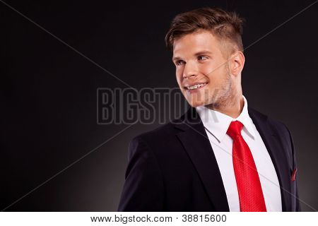 handsome young business man posing , looking over his shoulder and smiling, on a dark background