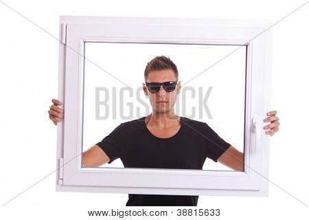 young man wearing sunglasses is holding a pvc window frame on white background