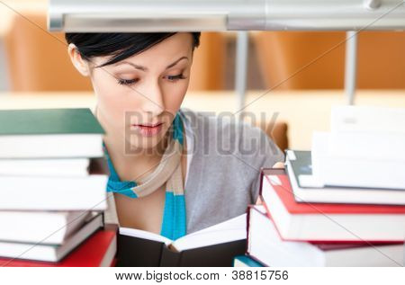Reading book female student surrounded with piles of books sitting at the desk at the library. Academic achievement