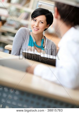 Woman communicates with man showing her something in the book sitting at the desk at the library