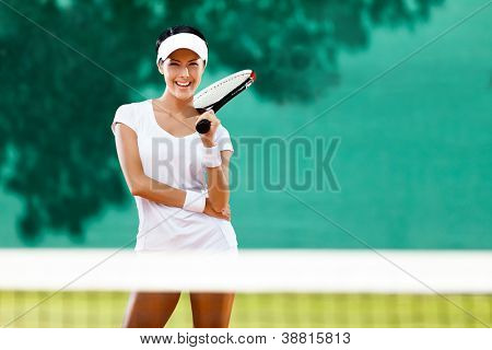 Young sportswoman with racquet at the tennis court. Healthy lifestyle