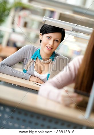 Smiley woman sits at the desk behind another one at the reading hall