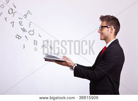 side view of a young business man holding a touch screen pad and looking up above it at some symbols and words coming out of it