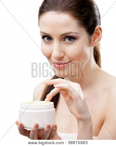 Woman holding emollient cream container and starting to apply cream, isolated on white