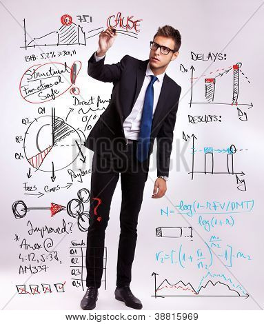 full body picture of a business man drawing or writing some graphs and diagrams with his marker, planning the future