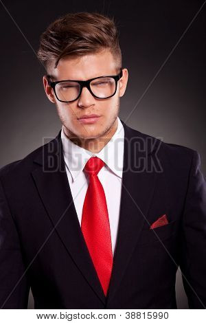 young business man looking furiously at the camera with angry eyes. dark background