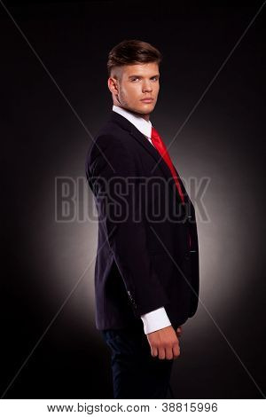side view of a young business man wearing a red tie looking into the camera, on dark background