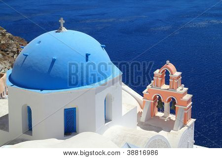 A church with a blue dome overlooks the spectacular caldera surrounding the beautiful island of Santorini, Greece