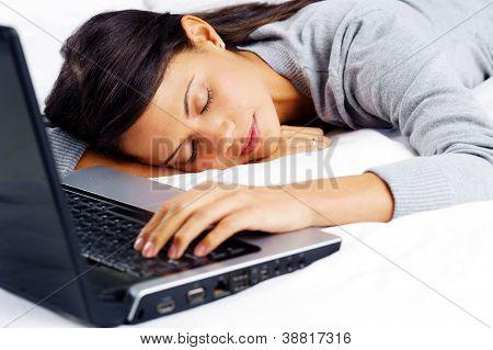 woman fallen asleep while using computer in bed at home
