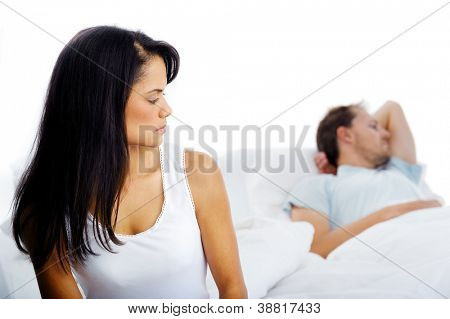 Couple fighting in bed, woman upset, thinking and man sleeping in background. unhappy relationship