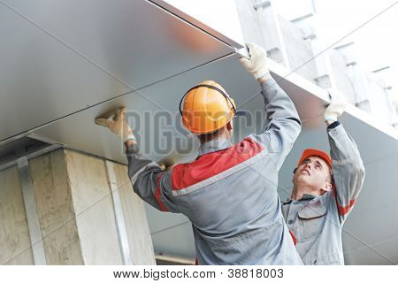 The Workers builders doing facade works with metal sheet boarding