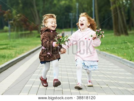 two happy little girls kids having fun while and laughing running in park racing against each other