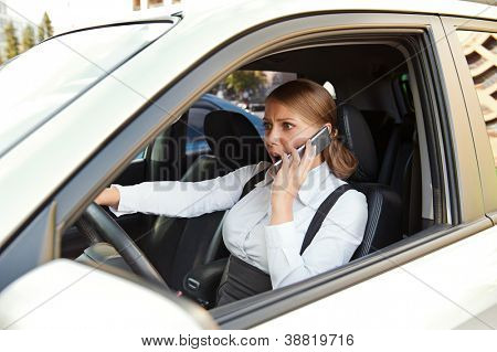 businesswoman driving the car and angrily talking on the phone