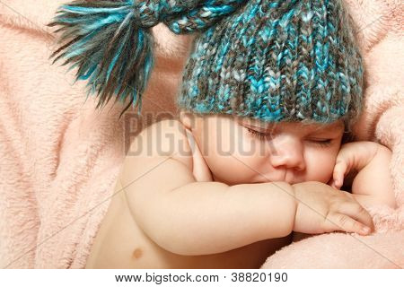 cute baby sleeping on pink plaid in funny hat, beautiful kid's face closeup with copyspace