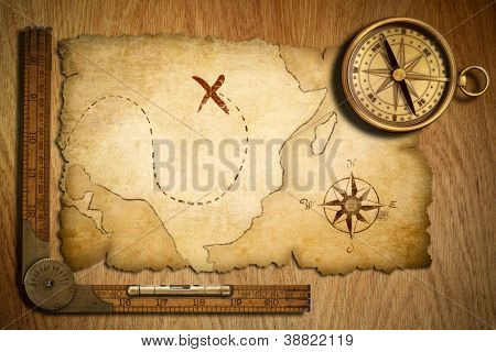 aged treasure map, ruler and old brass compass on wooden table top view