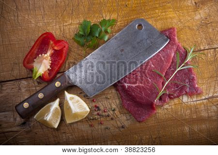 Butcher's still life with a cleaver, slices of raw beef and other stuff.