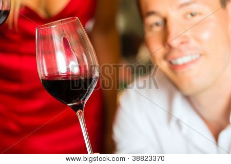 Man testing wine in background wine barrels in wine cellar