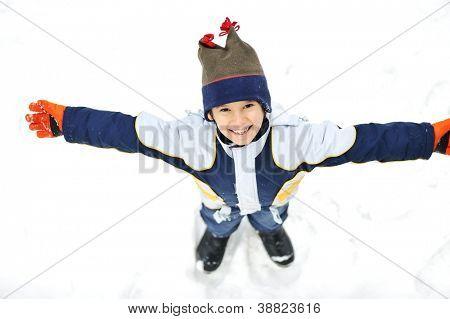 Happy child lies on snow ground