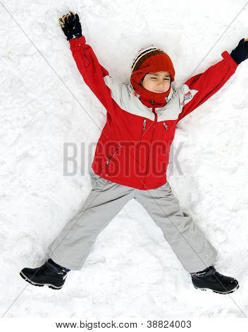 Happy kid lies on snow ground