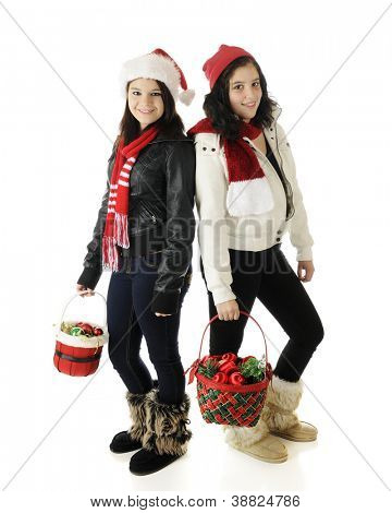 Two teen sisters, back-to-back, each in their outdoor outfits with Christmas hats and carrying a baskets of holiday ornaments.  On a white background.