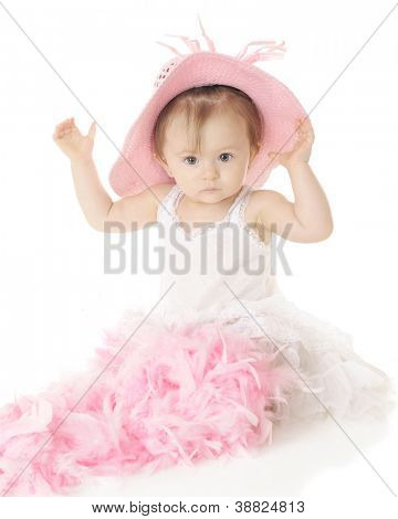 An adorable, serious baby girl in her petticoat.  A pink boa fills her lap, while she tries on a pink hat.  On a white background.