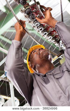 african american textile industrial technician repairing weaving machine