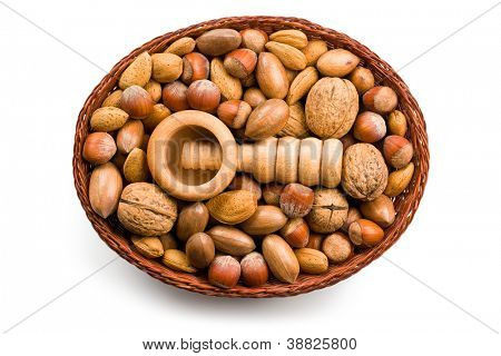 wooden nutcracker and nuts in basket on white background