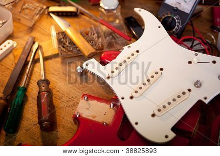 Red electric guitar on guitar repair desk or in a  repair work shop. Neck and pickguard detached. Double cutaway solid body guitar, red metallic color. Shallow depth of field.