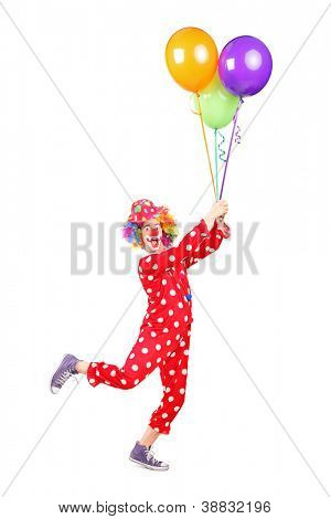 Full length portrait of a male clown holding balloons and flying isolated on white background