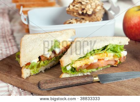 Plastic lunchbox being made with sandwiches on a wooden board