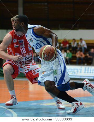 KAPOSVAR, HUNGARY - OCTOBER 20: Christopher Dunn (in white) in action at Hungarian Championship basketball game with Kaposvar (white) vs. Nyiregyhaza (red) on October 20, 2012 in Kaposvar, Hungary.