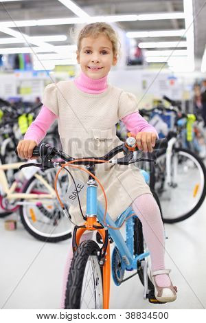 Smiling girl sits on bright bicycle and looks at camera in sports store.