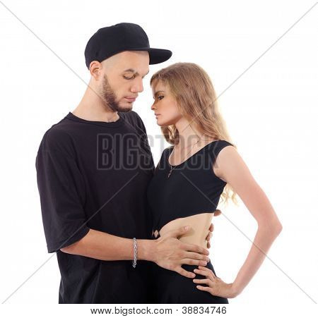Rapper wearing black t-shirt and hat hugs graceful girl isolated on white background.
