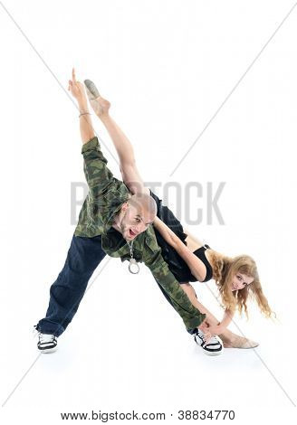 Happy rapper and gymnast girl depict triangle isolated on white background. Man points his finger up, woman raised one leg up.