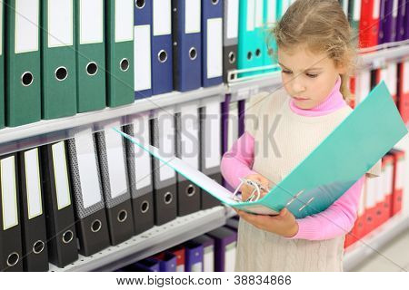 Serious looks at big green folder and stands near to shelves with folders.
