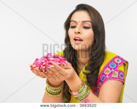 Woman Blowing Rose Petals Held In Her Plam